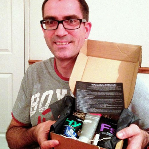 Picture of a happy subscriber holding up his shaving subscription box