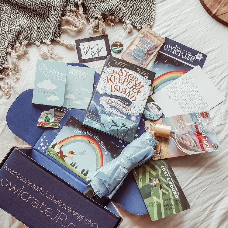 Owlcrate Jr box with books and bookish goods spilling out in a cozy setting.